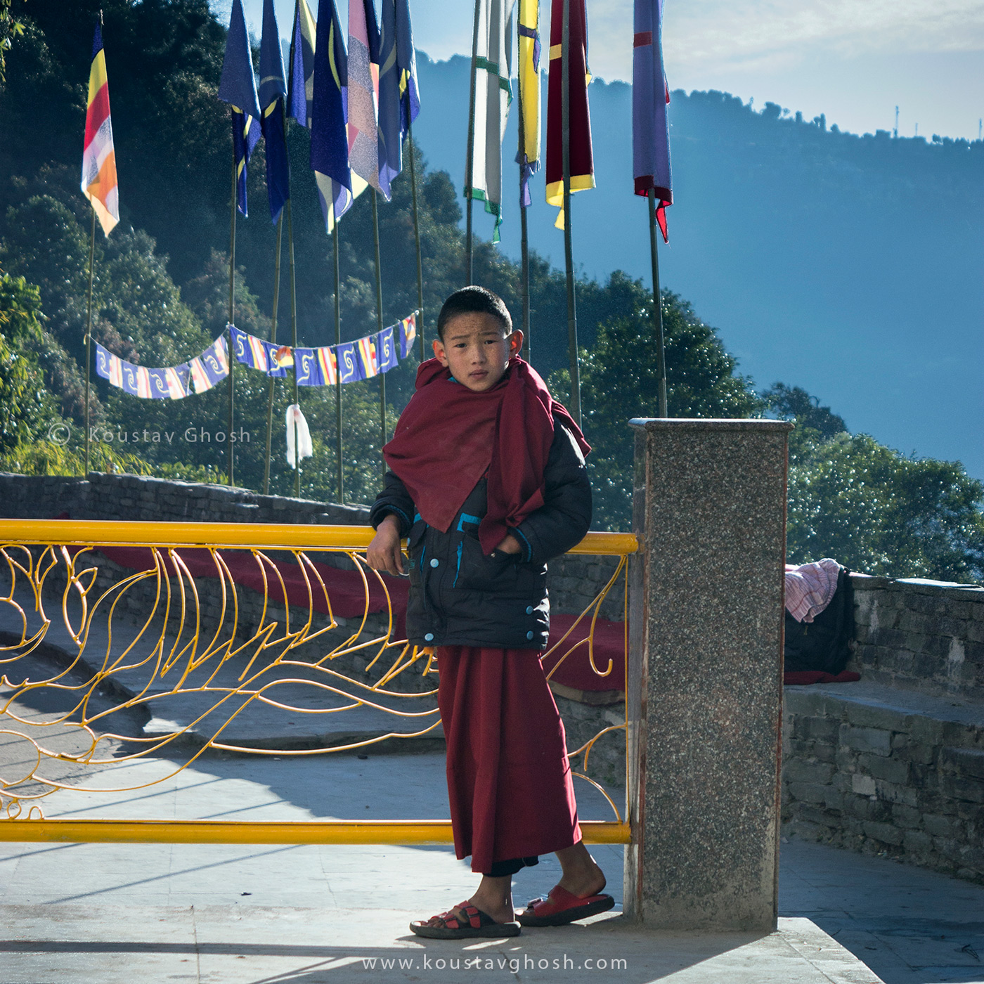 A young monk standing against the sun during Kagyed festival on early morning in old Ralang Monastery
